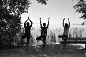 three girls decreasing anxiety by practicing yoga in nature